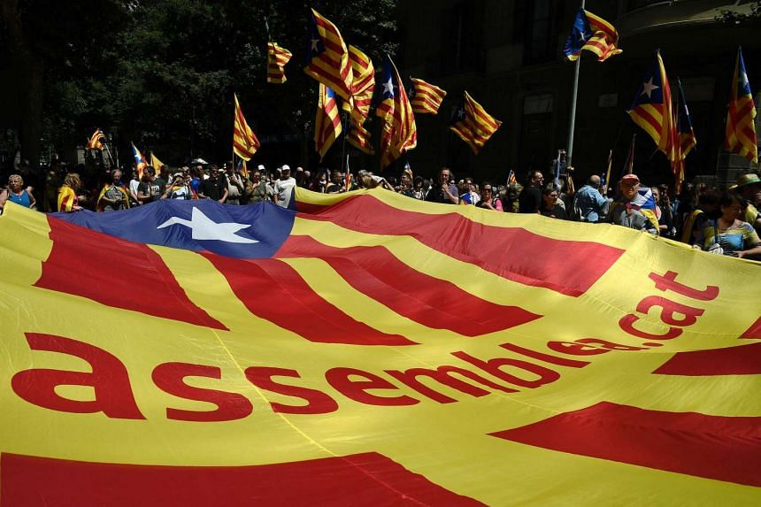 Protesters carry a giant independentist flag during a demonstration outside the Catalan government headquarters in Barcelona on May 29, 2016.