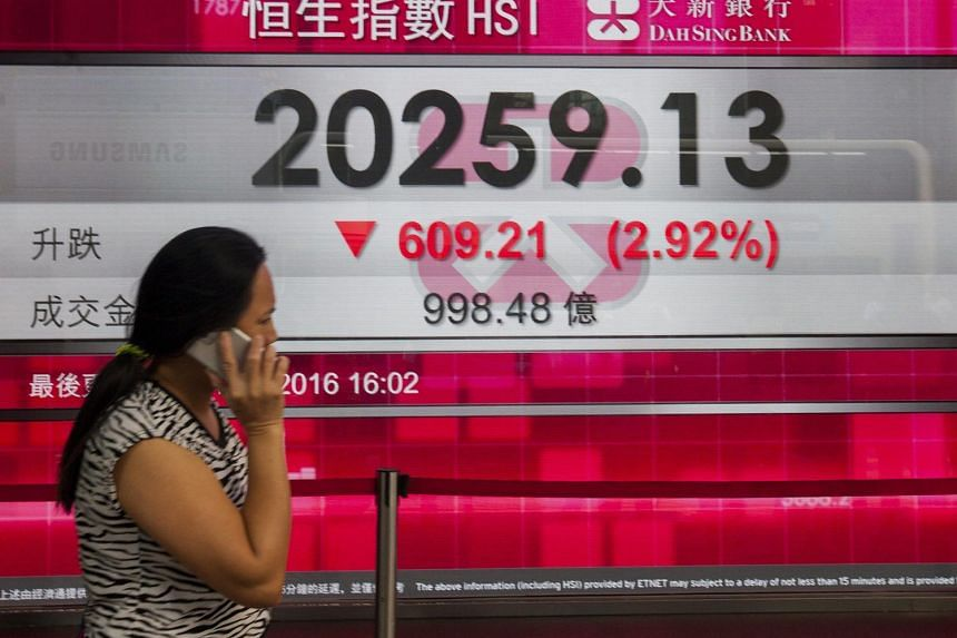 A woman walks past a bank board displaying the closing numbers of the Hang Seng Index, in Hong Kong, on June 24, 2016.