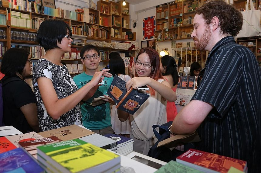Mr Jerome Lim and Mr James Miller chatting with Straits Times journalists Janice Heng (far left) and Charissa Yong at the book launch at Books Actually in Tiong Bahru.