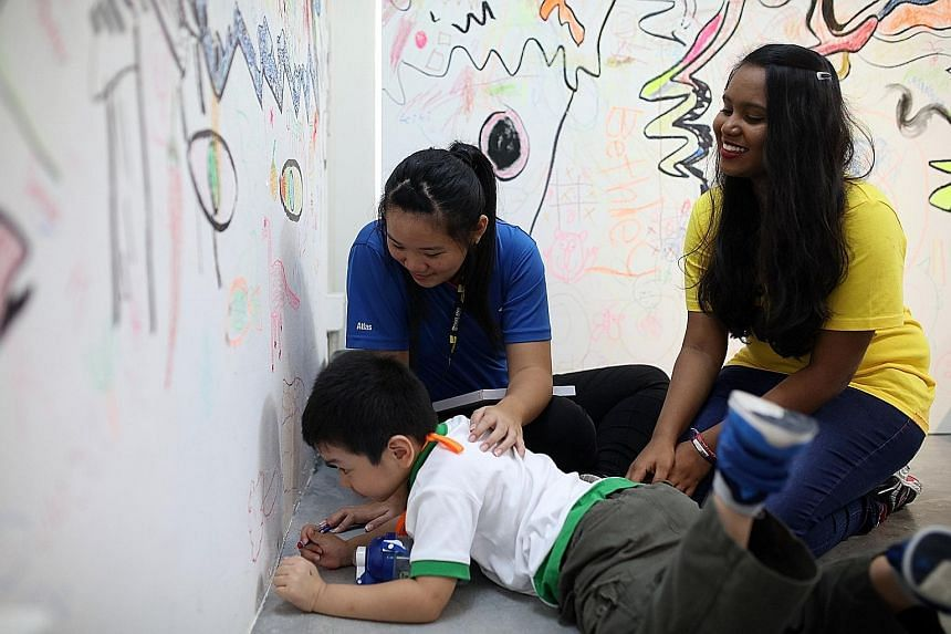 Ping Yi Secondary School student Vanessa Lian tries her hand at being a pre-school teacher at a workshop organised by Ngee Ann Polytechnic yesterday, accompanied by poly student facilitator P Usha Nantini.