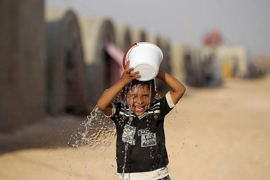 An internally displaced Syrian boy pouring water on his head to cool off in Jrzinaz camp, in the southern part of Idlib, Syria, this week. Temperatures have been creeping upwards in recent days, with the maximum expected to hit about 40 deg C today.