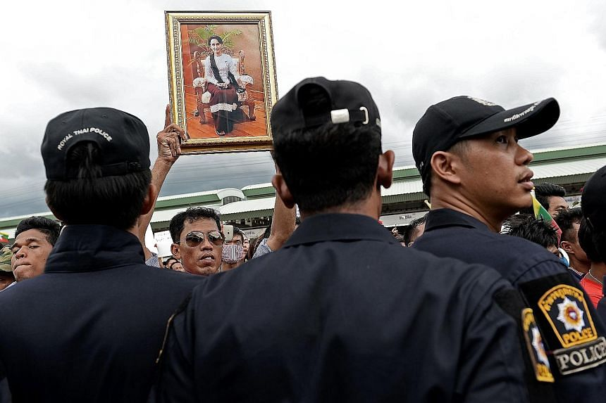 A Myanmar migrant worker holding up a portrait of Ms Aung San Suu Kyi while waiting for her arrival at a market in Samut Sakhon province near Bangkok yesterday.