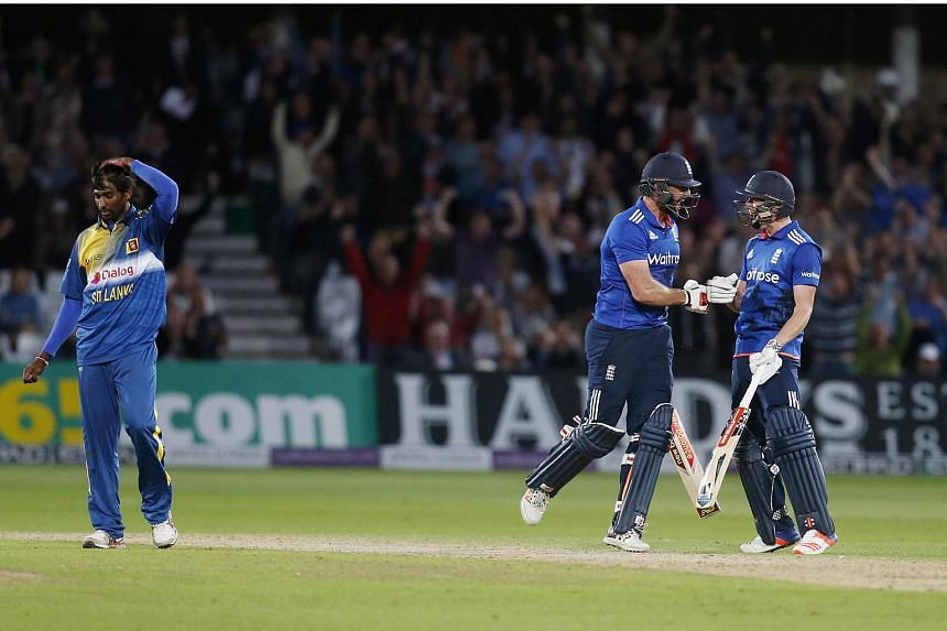England's Liam Plunkett (centre) celebrates with Chris Woakes after hitting a six from the last ball to draw the match.