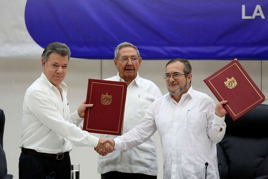 Colombian President Juan Manuel Santos (left) and FARC rebel leader Rodrigo Londono, also known as Timoleon Jiminez, shake hands in front of Cuban President Raul Castro, after signing the ceasefire, in Havana, Cuba, on June 23, 2016.
