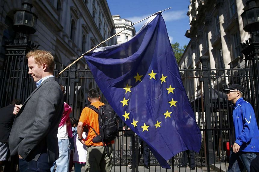 A man carries an EU flag, after Britain voted to leave the European Union, outside Downing Street in London, Britain June 24, 2016.