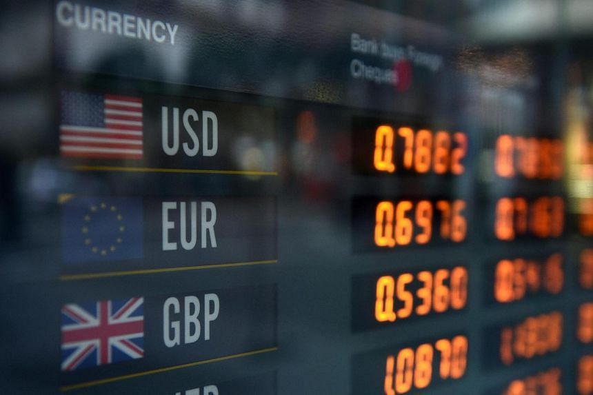 Foreign currency exchanges are seen on a board in Sydney on June 23.