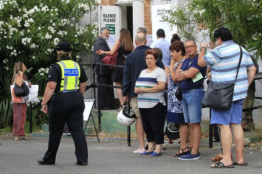 Several Gibraltarian voters wait to cast their ballot at a polling station in Gibraltar, on June 23, 2016.