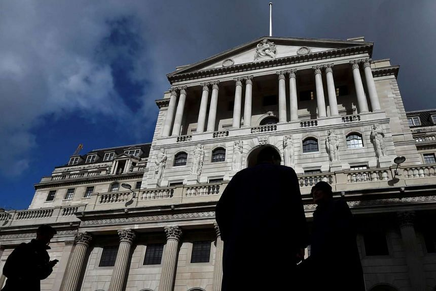 City workers walk past the Bank of England in the City of London, Britain, on March 29, 2016.