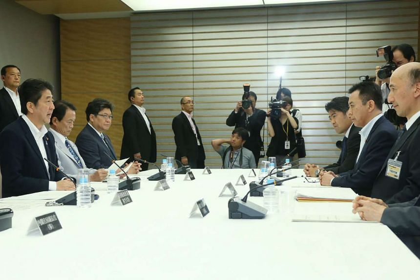 Japanese Prime Minister Shinzo Abe (left) speaks at a cabinet meeting on the national referendum in Britain, in Tokyo, on June 24, 2016.
