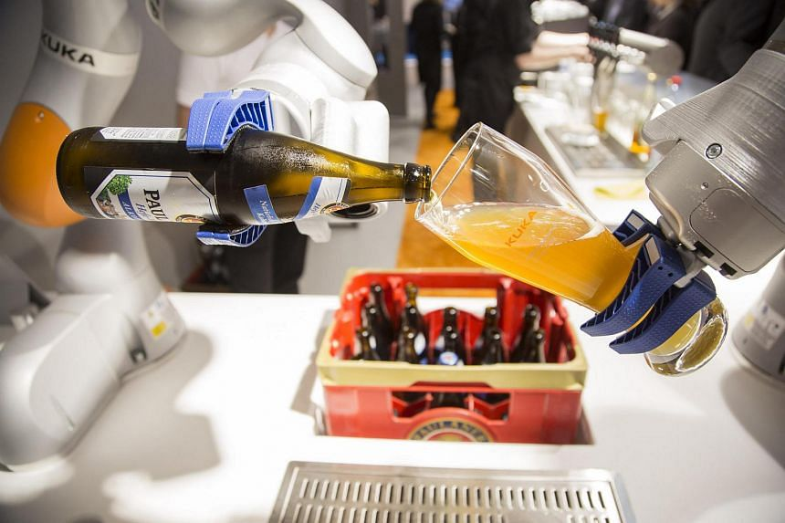 A Kuka industrial robotic arm pouring a glass of beer during a display at the Automatica trade fair in Munich, Germany, on June 21.