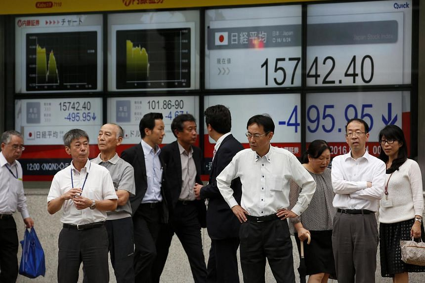 Pedestrians waiting to cross a road in front of an electronic stock board outside a securities firm in Tokyo on Friday (June 24).