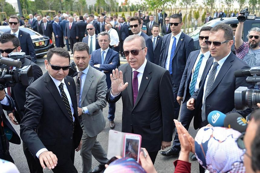 Turkish President Recep Tayyip Erdogan (centre) greets supporters as he arrives for the inauguration of the Bayzid I Mosque (Yildrim Bayezid) at the Esenboga International Airport in Ankara, on June 23, 2016.