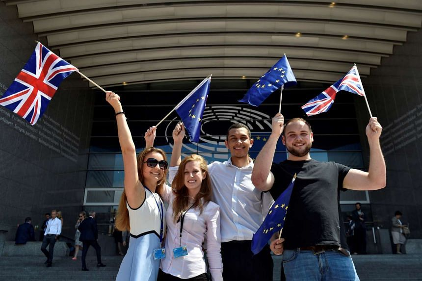 British students hold British and European Union flags in front of the European Parliament in Brussels, Belgium, June 23, 2016.