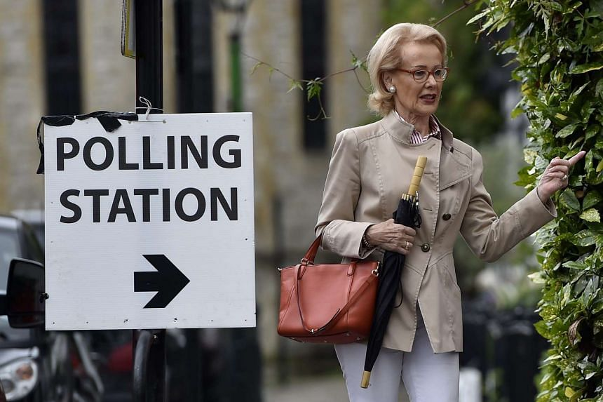 A woman enters a pub used as a polling station to vote in the EU Referendum in London, Britain, 23 June 2016.