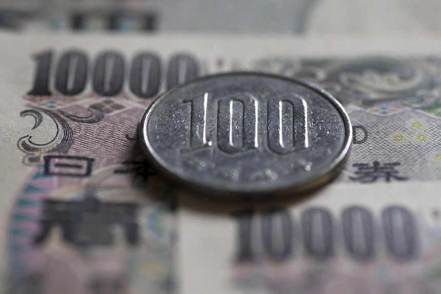 A Japanese 100 yen coin and 10,000 yen banknotes are arranged for a photograph in Tokyo.