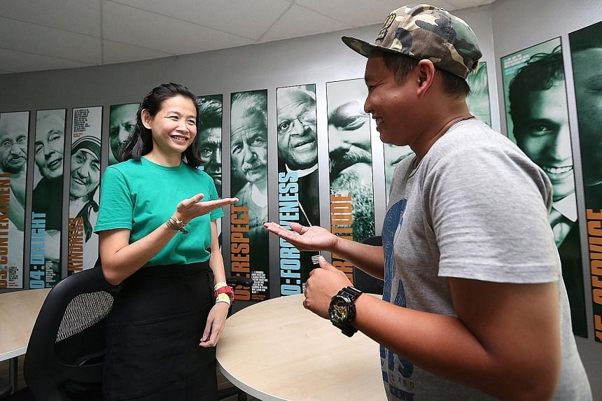 Far left: Candles, tea and silence to encourage mindfulness. Left: TeaRista Kim Chong demonstrating with Mr Muhammad Khairulanam Zamri how she communicates with participants using sign language.