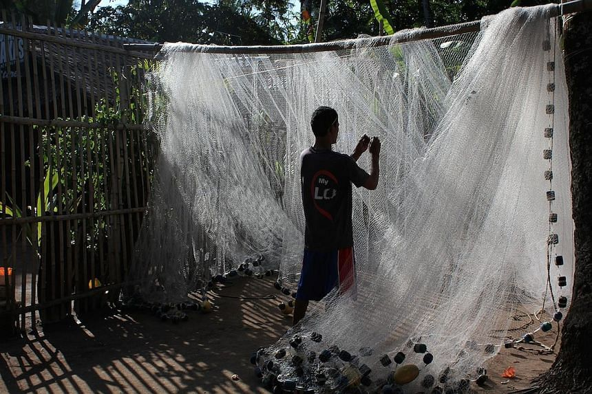 A torn fishing net being repaired. On their days off, fishermen bring up any discarded nets they find on the sea floor.