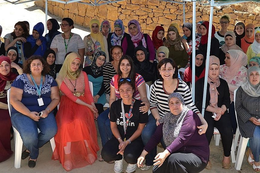 Ms Saba and a group of beneficiaries during a visit of Unicef officials in Akkar. Ms Saba leads Akkar Network for Development, an organisation that seeks to protect women and teenage girls from violence.