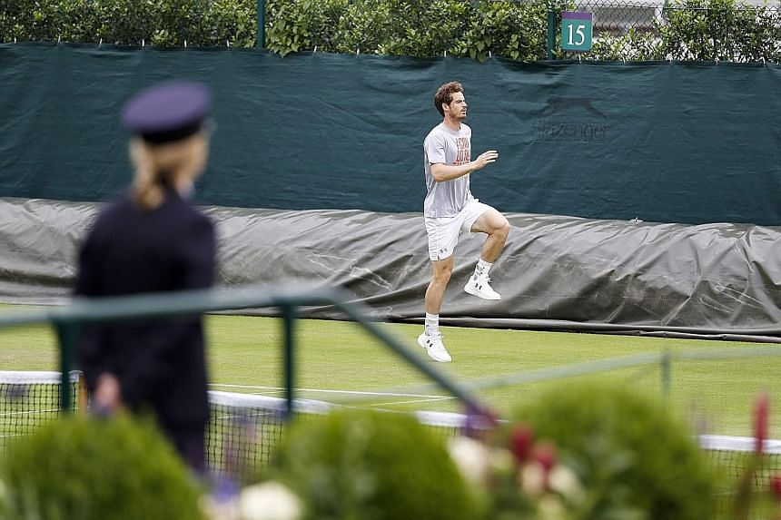 Andy Murray, the 2013 champion, warming up before training at Wimbledon while being watched by a member of the security staff. He is tipped to face world No. 1 Novak Djokovic in the final.