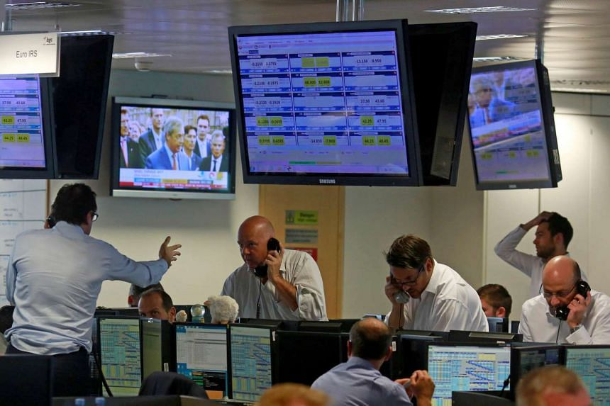 Traders from BGC, a global brokerage company in London's Canary Wharf financial centre, react during trading on June 24, 2016.