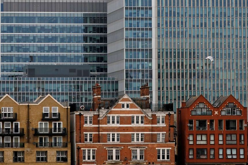 Apartment buildings are backdropped by skyscrapers of banks at Canary Wharf in London, on Oct 30, 2015.