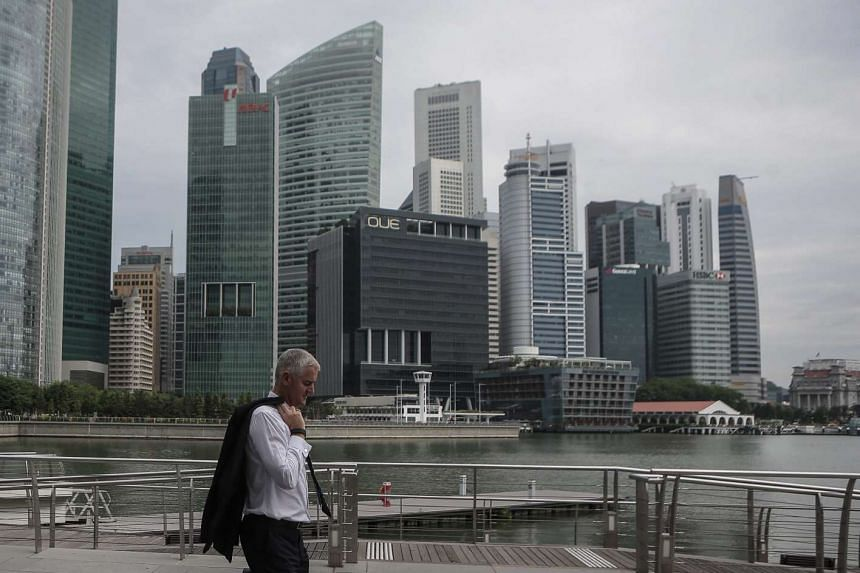 A man with a blazer draped over his shoulder walks past buildings in the financial district of Singapore, on June 23, 2016.