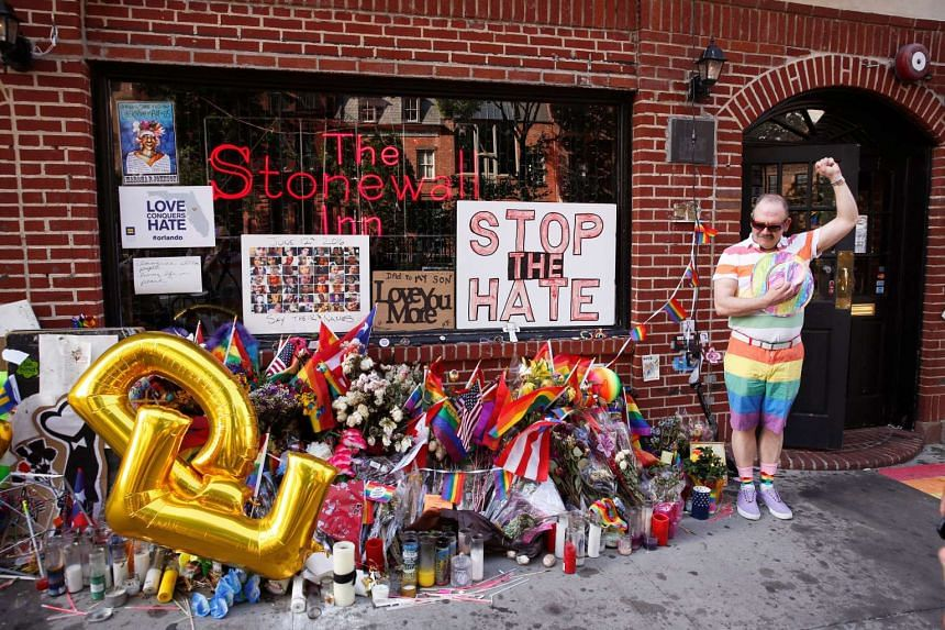 A man poses for a friend's photograph near a memorial to the victims of the Orlando shooting, outside the Stonewall Inn in New York, US on June 24, 2016.