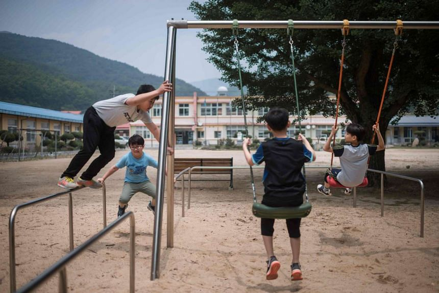 Four of Seoksan Elementary School's six pupils play in an empty playground in the school, in Gunwi, about 200km south of Seoul.