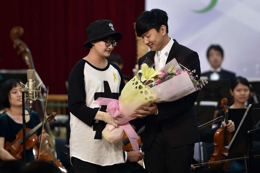 Singapore singer JJ Lin (right) receiving flowers from a victim injured in last year's water park explosion, after performing at a music concert in Taipei to mark the accident's first anniversary.