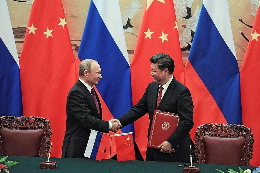Russian President Vladimir Putin and Chinese President Xi Jinping at a signing ceremony after their meeting in Beijing yesterday. Mr Putin is forging closer ties with China at a time when Russia is in need of trade because of Western sanctions impose