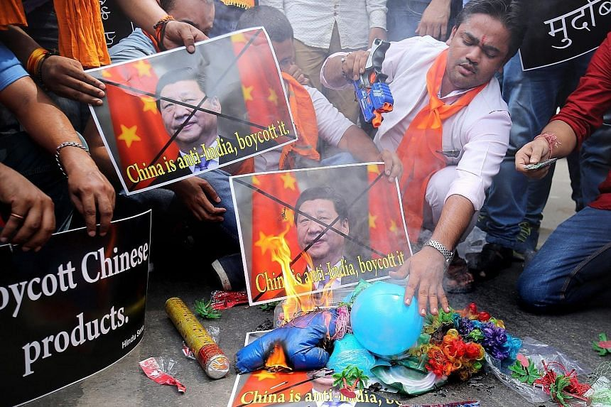 Indian activists from the right-wing Hindu Sena group burning posters of Chinese President Xi Jinping during a protest yesterday over China's perceived anti-India bias in the Nuclear Suppliers Group.