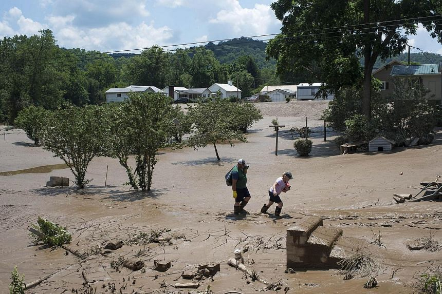 People trudge through the mud left over from the flooding of the Elk River along State Route 119 in Falling Rock, West Virginia.