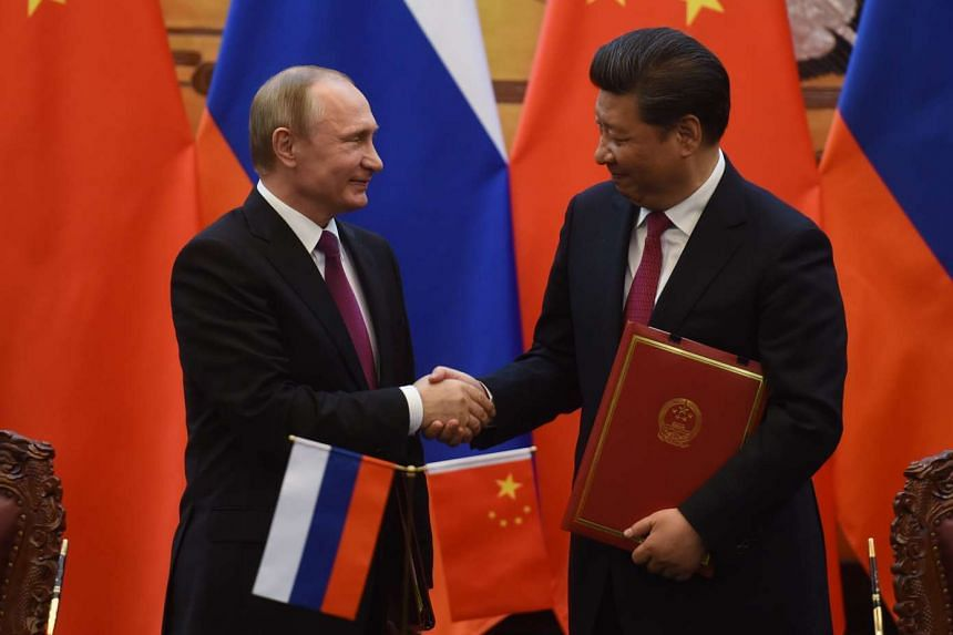 Putin and  Xi shake hands  at the end of a joint press briefing in Beijing's Great Hall of the People on June 25, 2016.