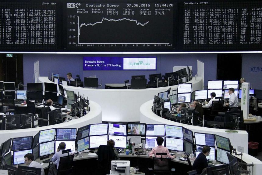 Traders work at their desks in front of the German share price index, DAX board, in Frankfurt, on June 7, 2016.