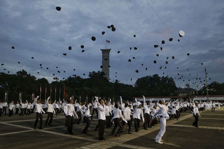 New officers tossing their peaked caps at the end of the Officer Cadet Course Commissioning Parade at SAFTI Military Institute on June 26, 2016.