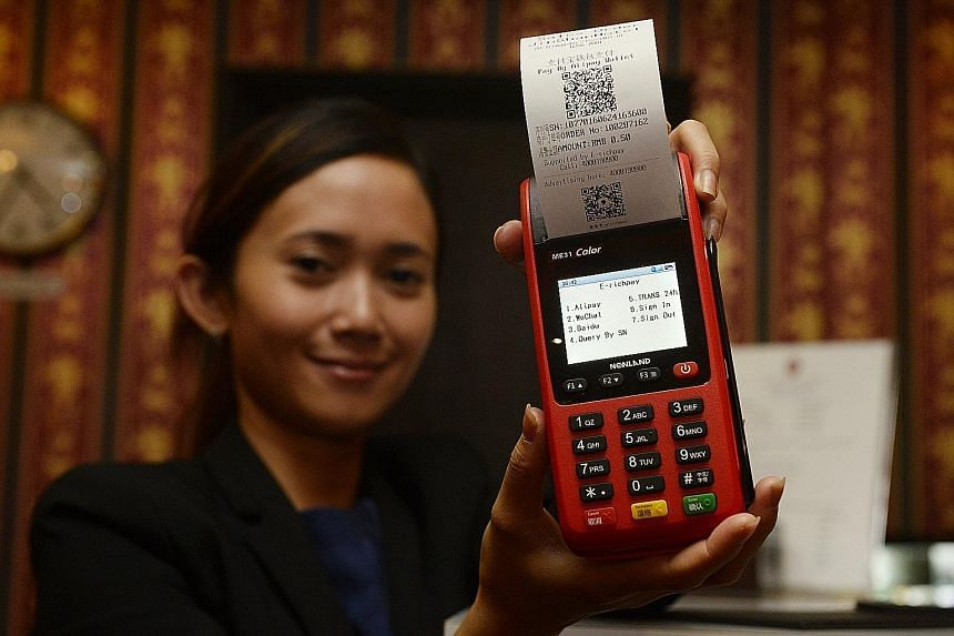Jinshan Hotel manager Amelia Wahjoto with SwiftPay's terminal that accepts four types of platforms - WeChat Pay, Alipay and Baidu, and UnionPay cards.