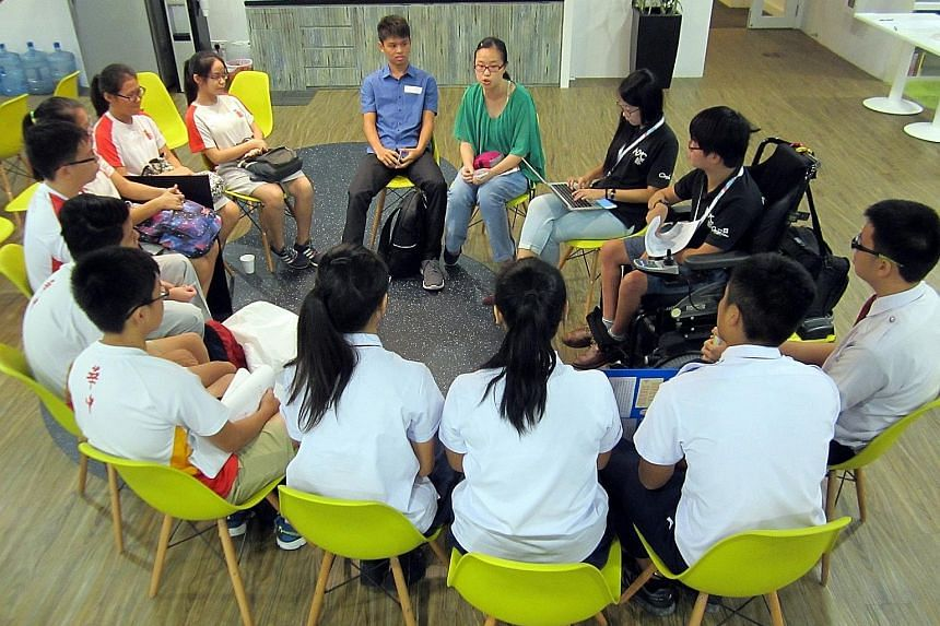 Lim Kia Teng (in green) and Teoh Jing Yang (in blue), both 17 and students of NUS High, presenting their project idea to other applicants recently.