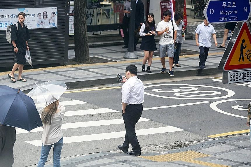 """""""Smartphone zombies"""" spotted at a main pedestrian crossing near Seoul's City Hall last week, oblivious to the warning signs."""
