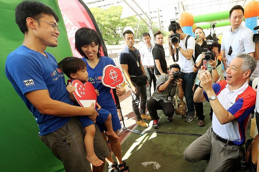 Prime Minister Lee Hsien Loong played photographer yesterday at the Teck Ghee Family Day, as he shot a family portrait for Mr Low Kang Yin, 37, his wife Ong Lizhen, 34, and their 19-month- old son Valen. Known for being a photo buff, Mr Lee took phot