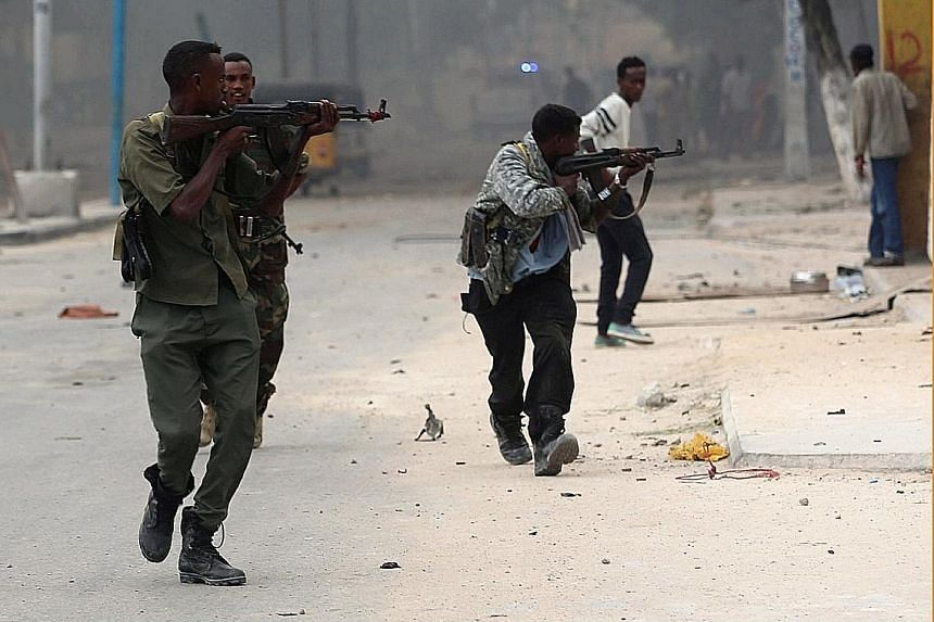 Somali government soldiers running to take their positions amid gunfire after a bomb was detonated near the entrance of the Nasa Hablood hotel in Mogadishu.