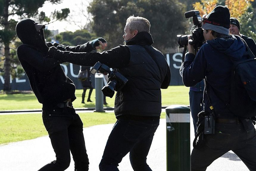A demonstrator scuffling with a photographer during a rally outside Parliament House in Melbourne yesterday. Victoria state plans to impose stiffer penalties on mask-wearing protesters.