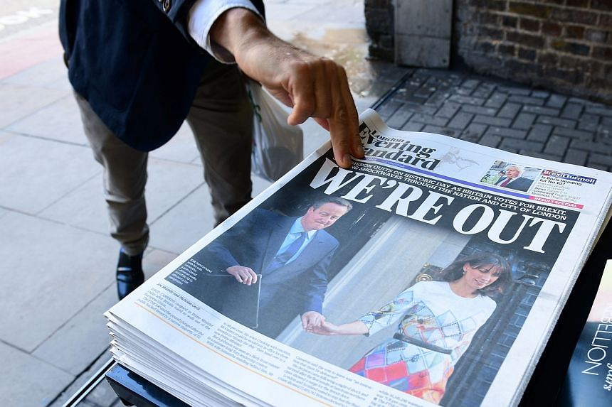 A man takes a copy of the London Evening Standard with the front page reporting the resignation of British Prime Minister David Cameron and the vote to leave the EU in a referendum, on June 24.