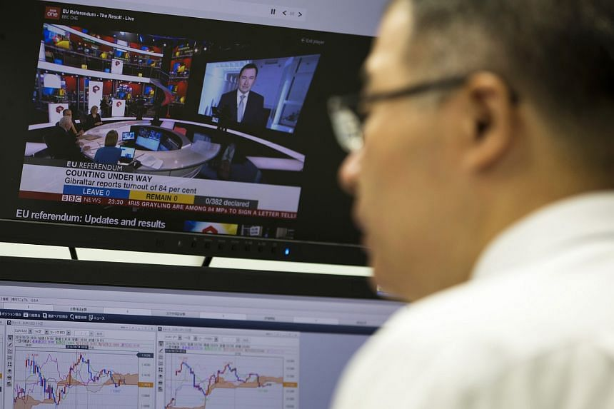 An employee works, as live news programme reporting on the European Union referendum, at a foreign exchange brokerage in Tokyo, Japan, June 24.