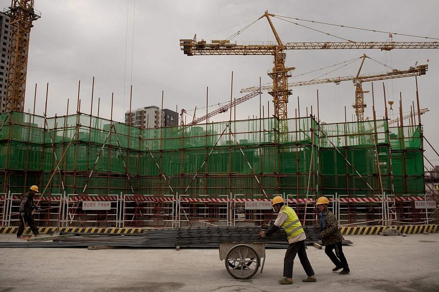 Labourers work at a construction site in Beijing on May 31. China's May industrial profit growth eases to 3.7% year on year.