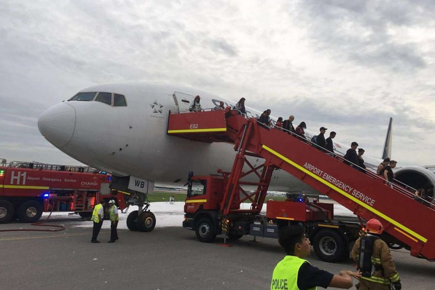 Passengers disembarking from flight SQ368 that caught fire on the runway at Changi Airport on Monday (June 27) morning.