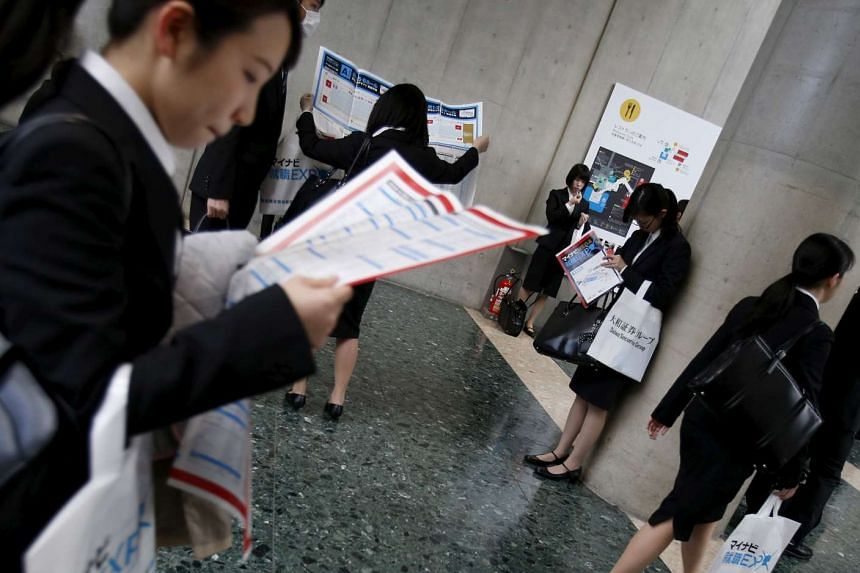 Female job seekers look at maps of a job fair held for fresh graduates in Tokyo on March 20, 2016.