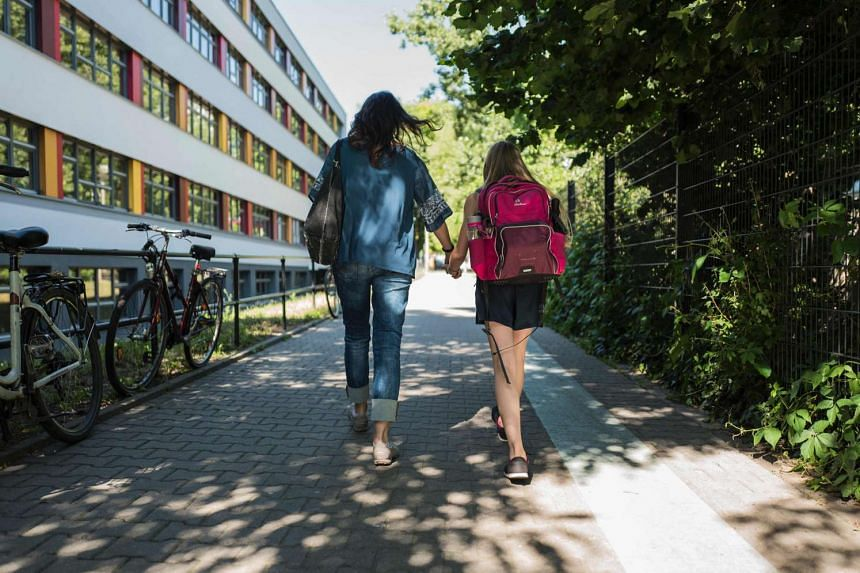 A woman walks with her 11-year-old daughter after picking her up from school in Berlin, on June 23, 2016.