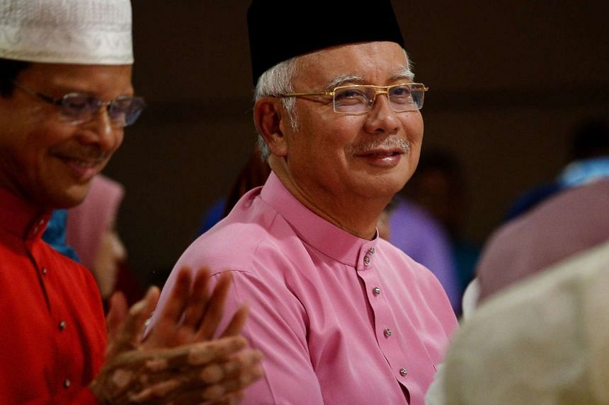 Malaysia's Prime Minister Najib Razak (right) looks on during a Ramadan event at the Putra mosque in Putrajaya, on June 25, 2016.