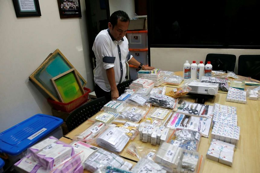 An officer from the National Police Criminal Investigation department looks at evidence confiscated from raids linked to fake vaccines production and distribution in Jakarta on June 27, 2016.