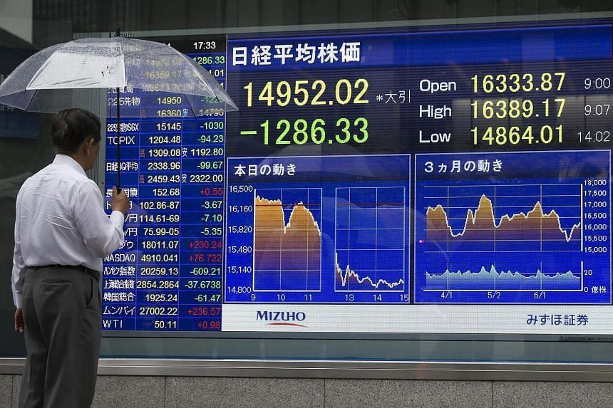 A pedestrian holding an umbrella looks at an electronic stock board displaying the closing figure of the Nikkei Stock Average outside a securities firm in Tokyo.